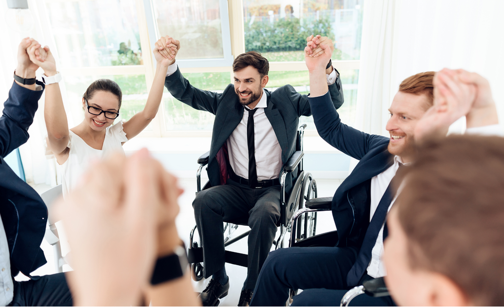 man in wheelchair and coworkers join hands